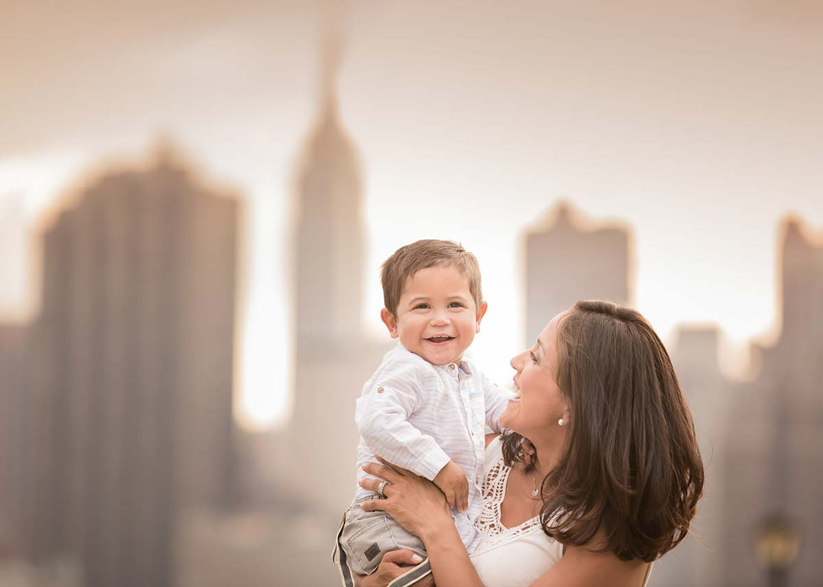 Happy mother holding her baby boy near the NYC skyline