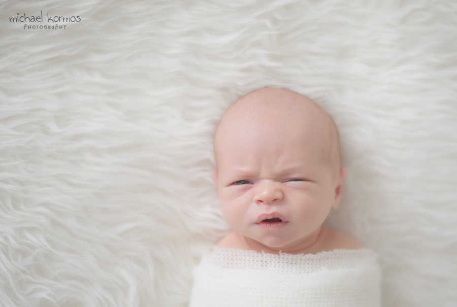 newborn making silly faces for the camera on a sheepskin blanket