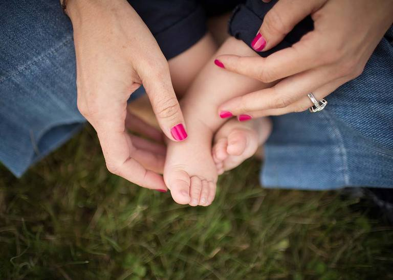 Closeup image of mother's hands holding her son's baby feet.
