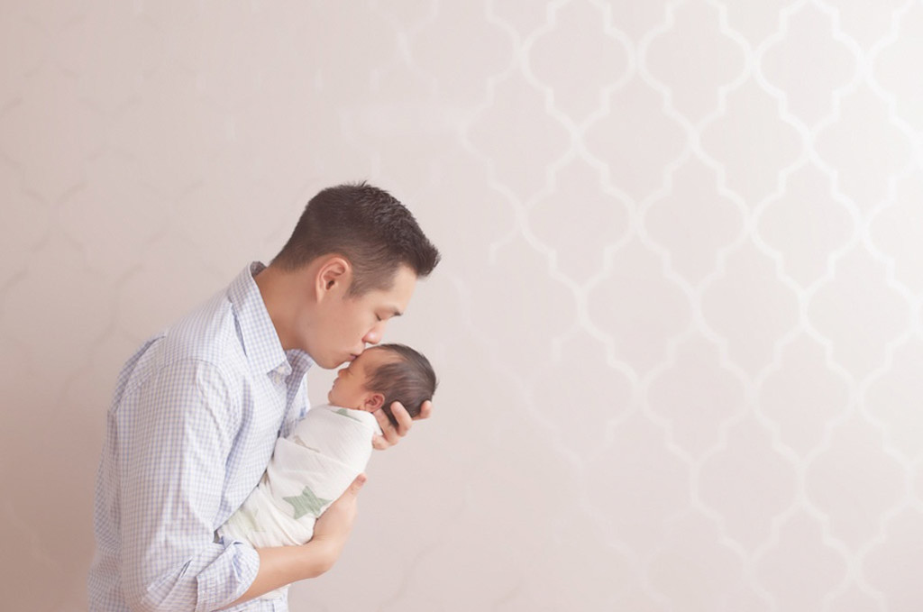 father kissing newborn on forehead