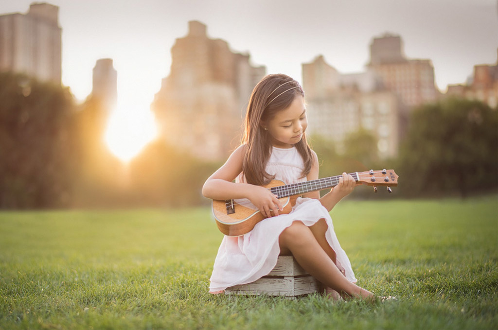 girl playing ukelele at sunset