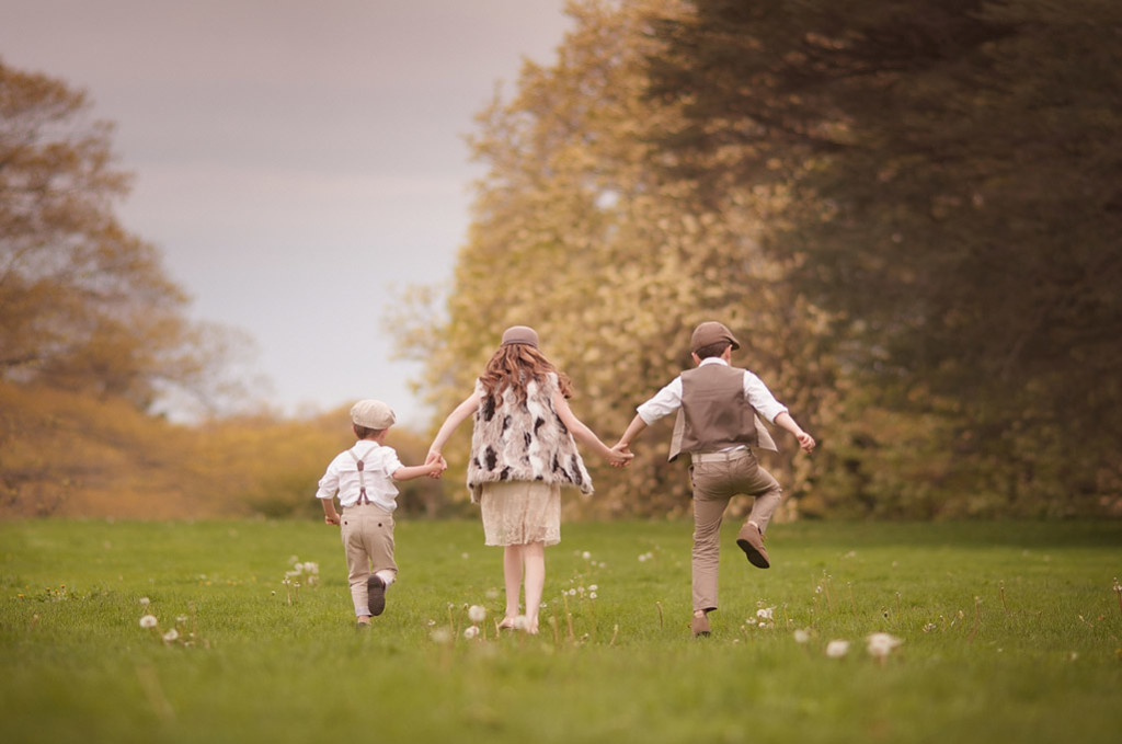 three children skipping through long island fields