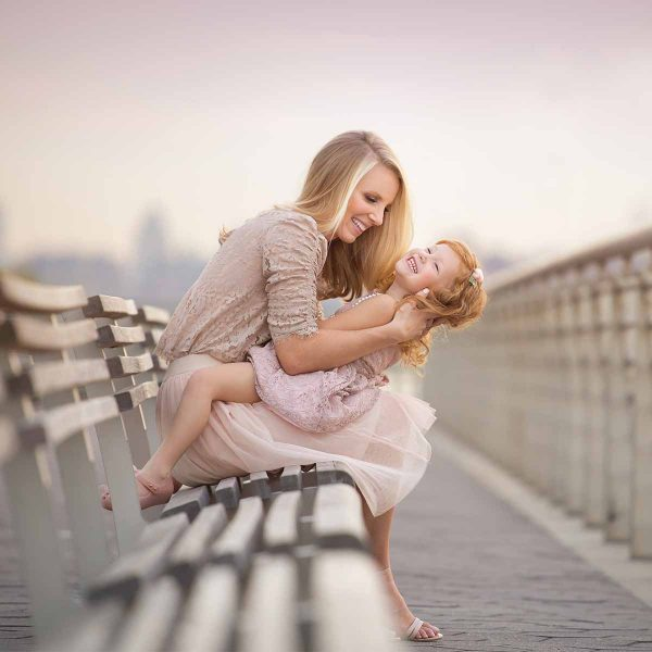 Mother playing with her daughter on a bench at a riverfront park in NYC