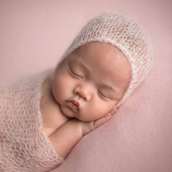 Closeup of a sleeping newborn with a knit hat