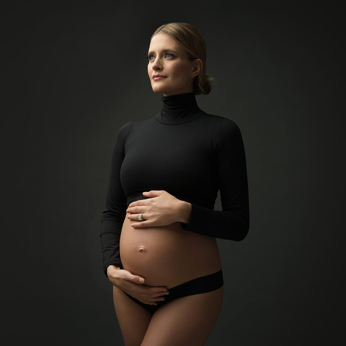 elegant pregnancy pose with black crop top photographed in maternity studio nyc