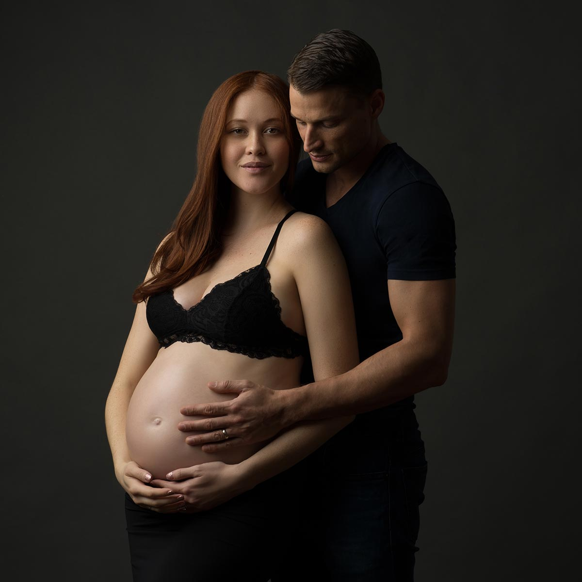 husband holding pregnant belly nyc studio maternity photo shoot