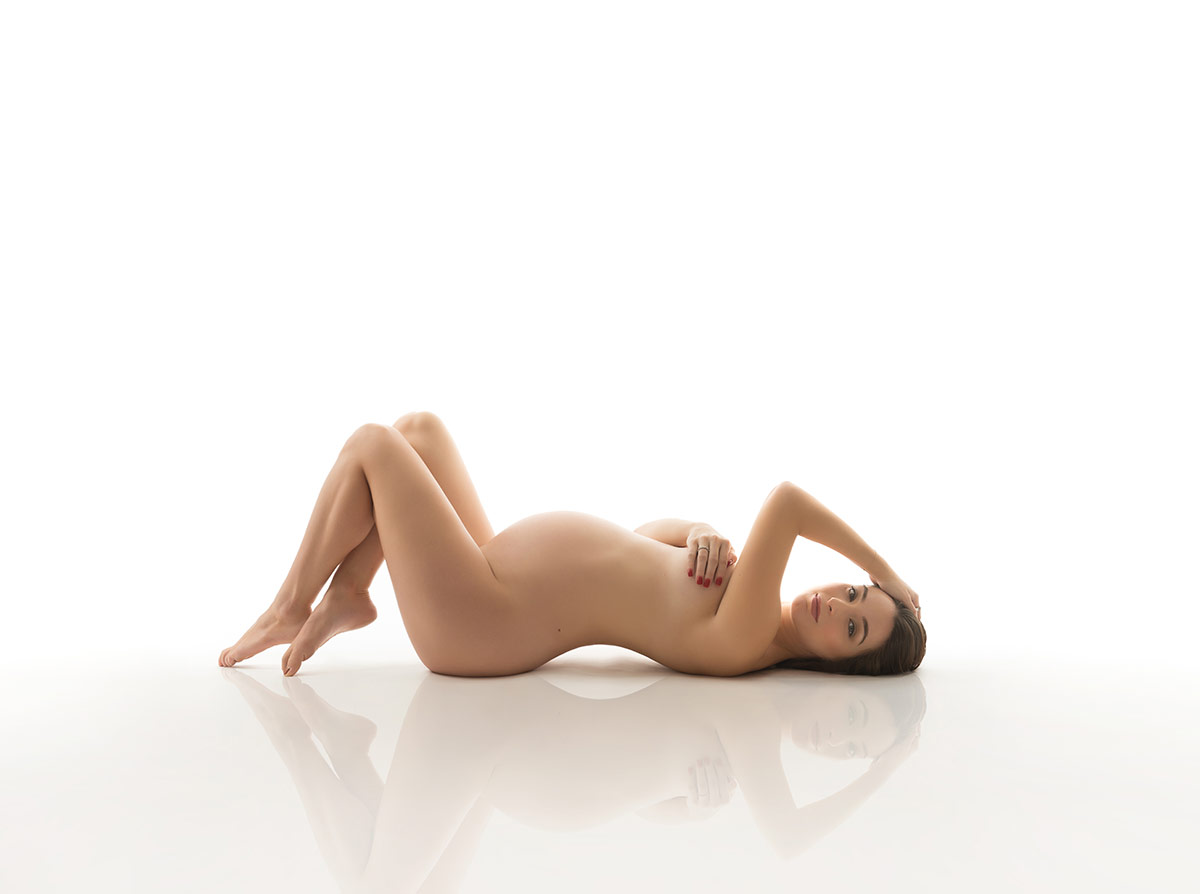 pregnant semi nude on white with reflection of maternity portrait