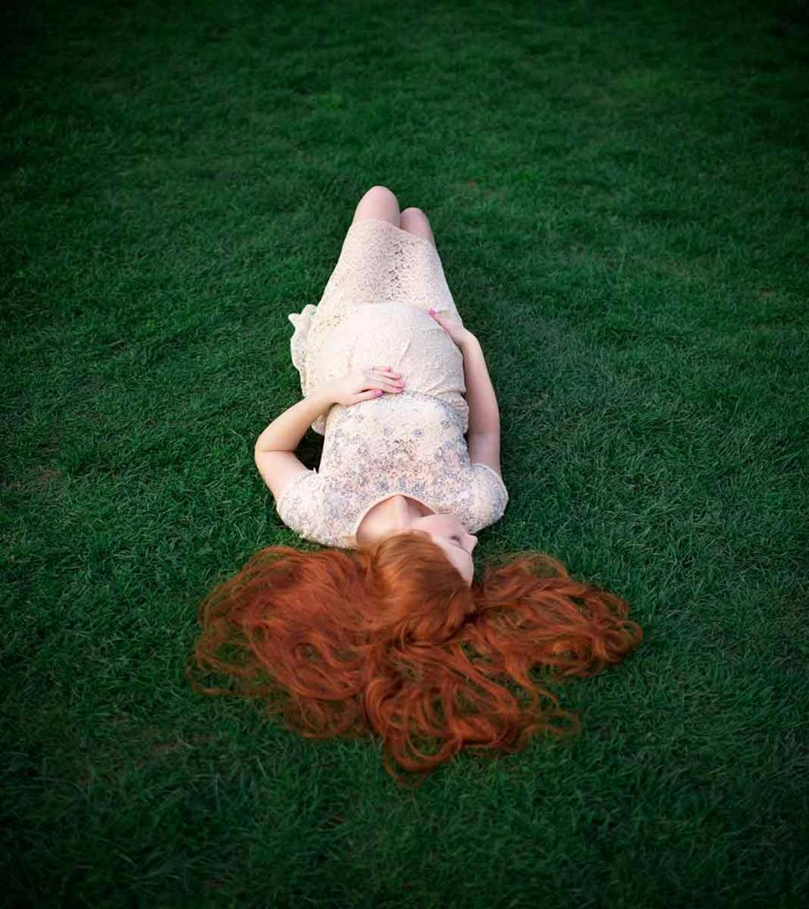 Pregnant woman with red hair laying in grass, cradling her belly.