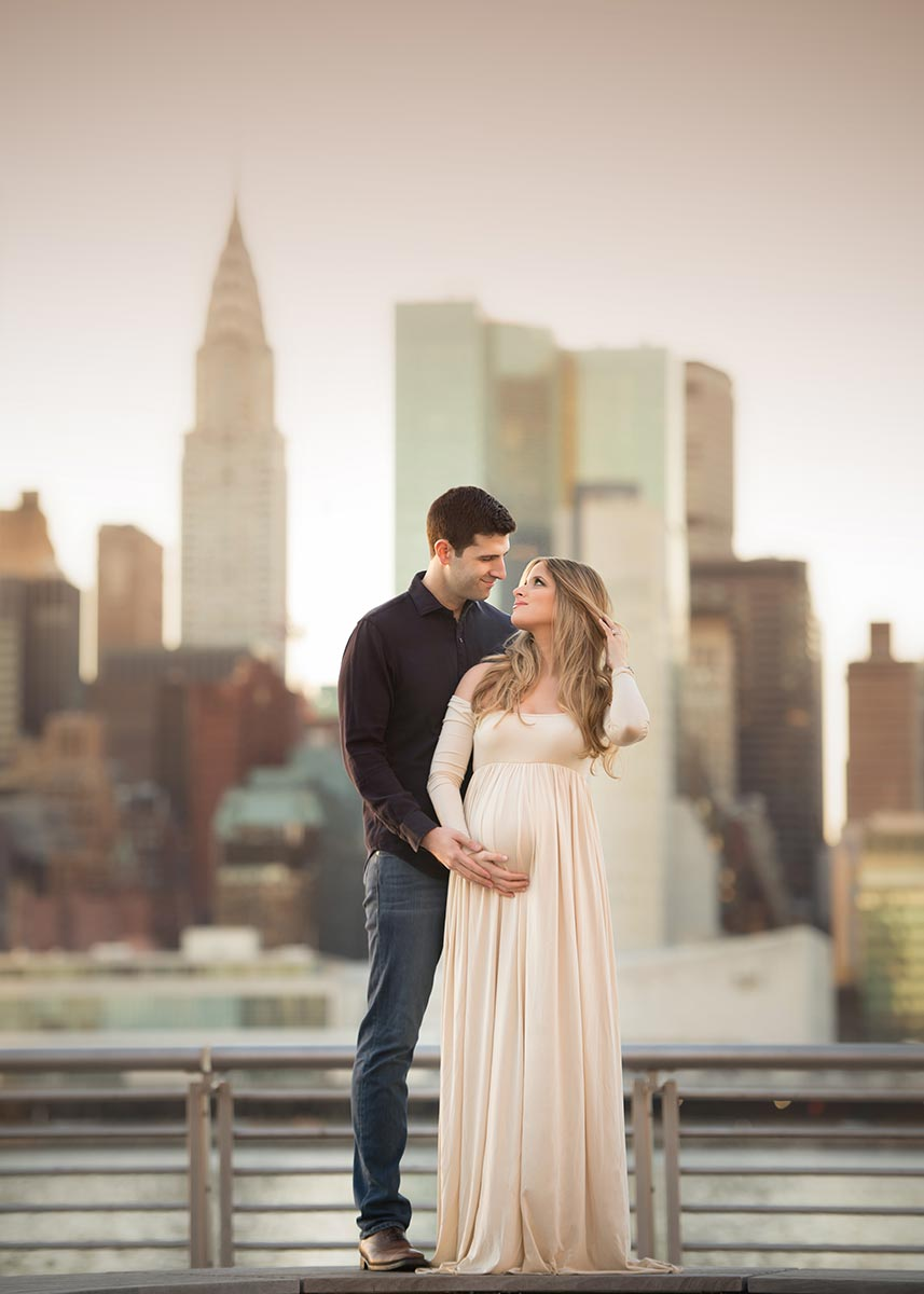 A man holding hands with his wife, and cradling her pregnant belly with the Chrysler building in the back.