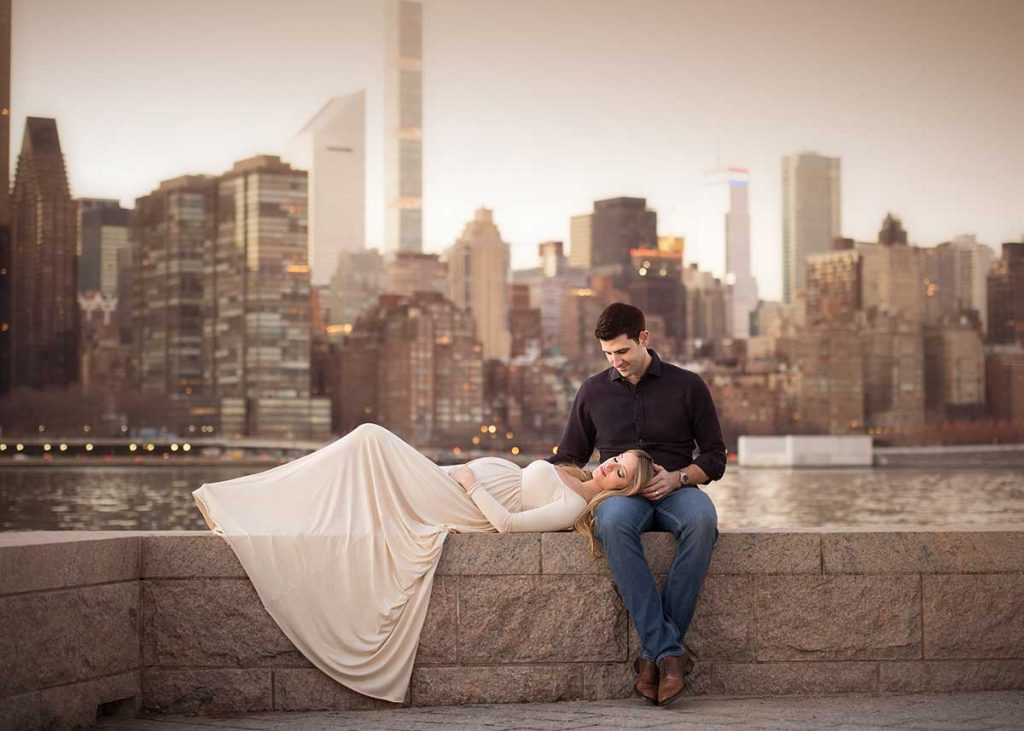 Couples portrait of a pregnant woman and her husband with NYC skyline.