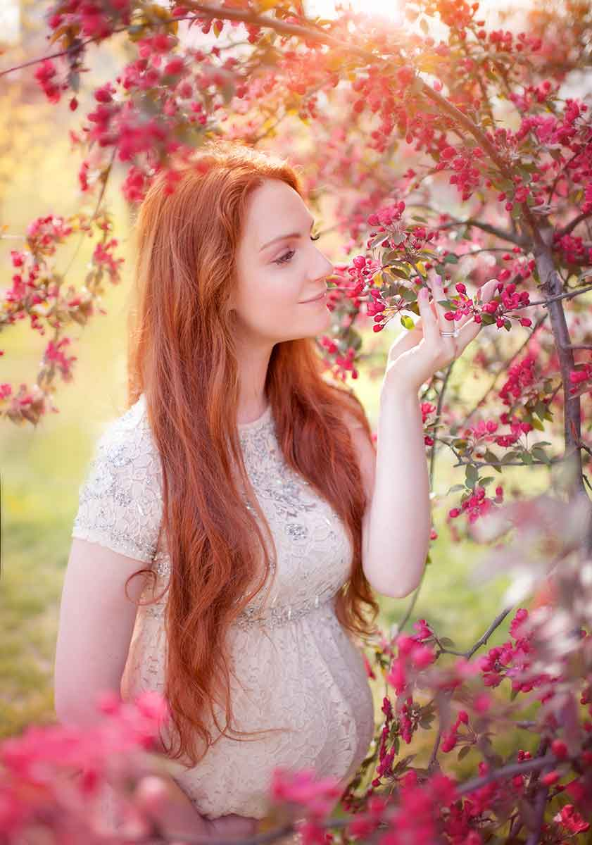 Closeup maternity portrait of a woman with red hair and cherry blossoms in NYC.