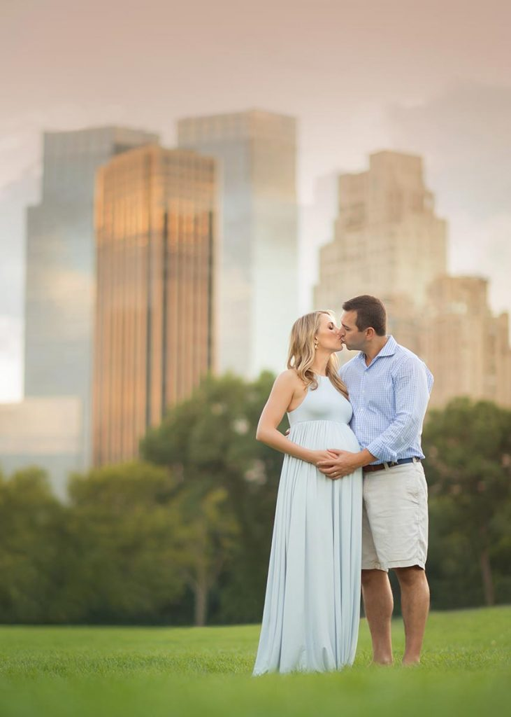 A husband and wife kissing in NYC's Sheep Meadow while cradling a pregnant belly.