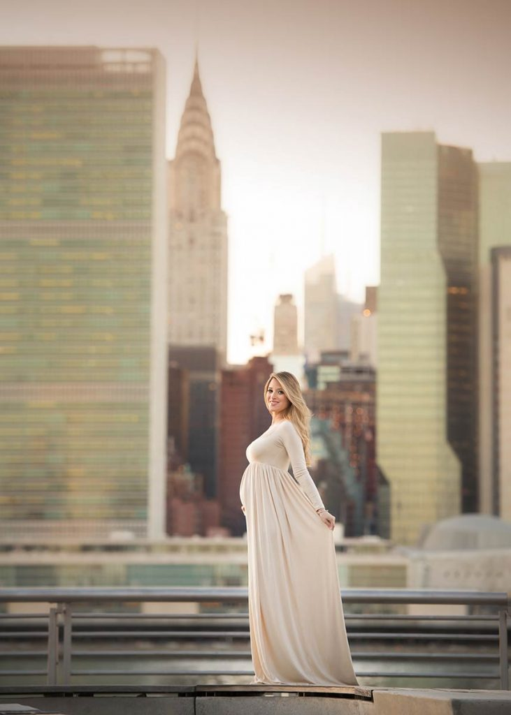 Young blonde woman, posing for a maternity portrait wearing a beige dress with the NYC skyline in the background.