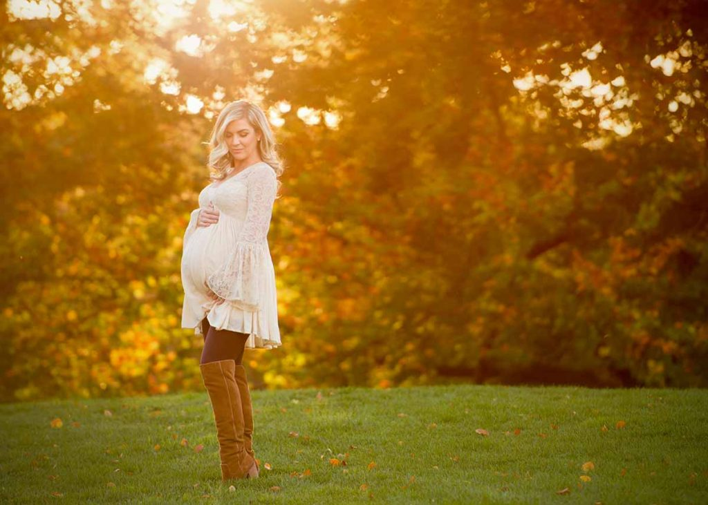A blonde woman in boots and beige dress cradling her pregnant belly while posing for a maternity portrait in NYC.