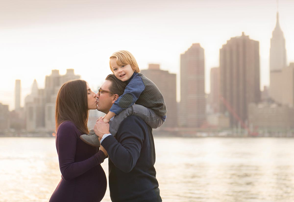 Man and a pregnant woman kissing while holding their sun near NYC's picturesque skyline.