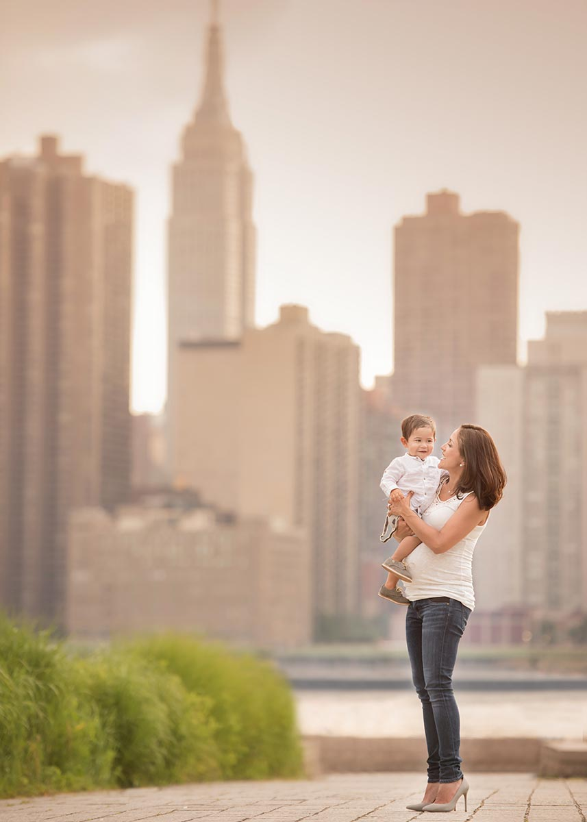 Pregnant Mother holding her son with the Empire State Building in the background.