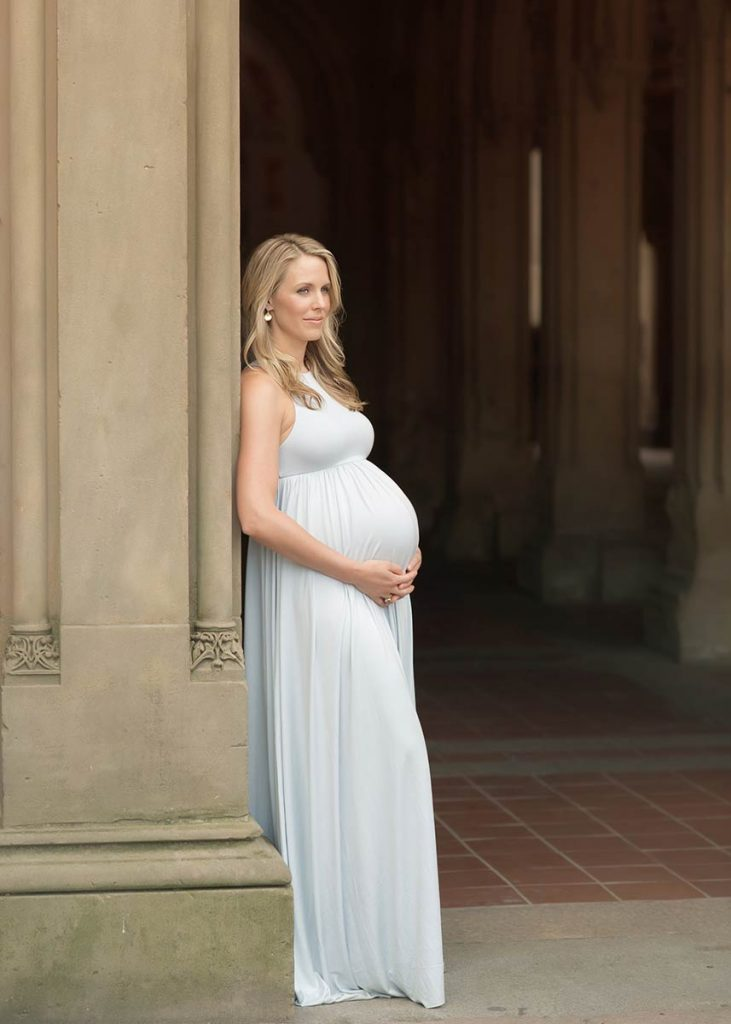 Blonde woman in a blue dress posing for a maternity photo in New York's Bethesda Fountain, Central Park.