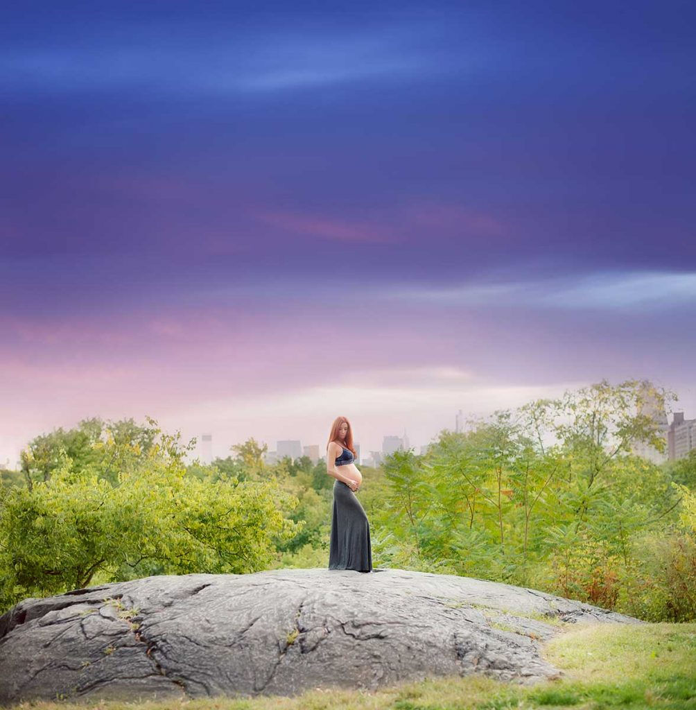 Maternity photo showing a woman standing on top of a rock in New York's Central Park during sunset.
