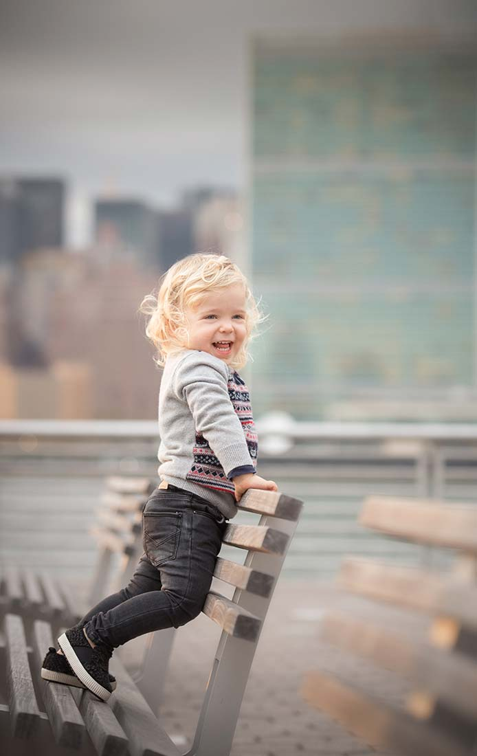Blonde boy standing and smiling on a park bench in NYC.