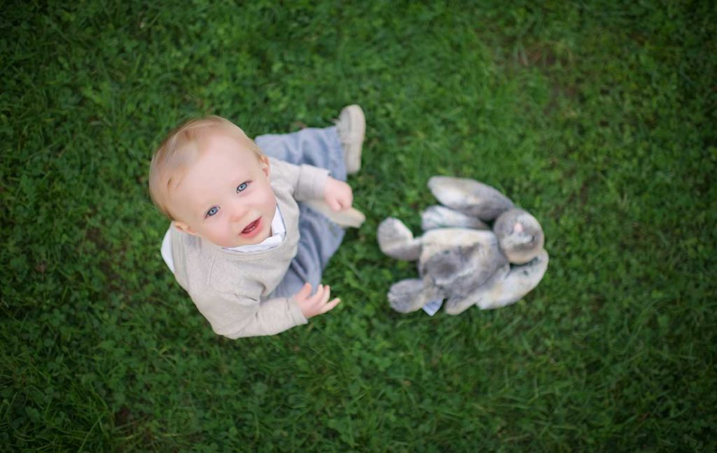 A boy sitting in grass along with his bunny and looking up.