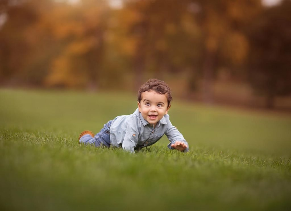 Happy boy crawling through a grass field.