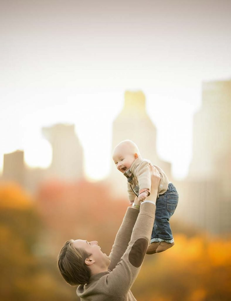 Father holding his baby boy up in the air with NYC skyline behind them.