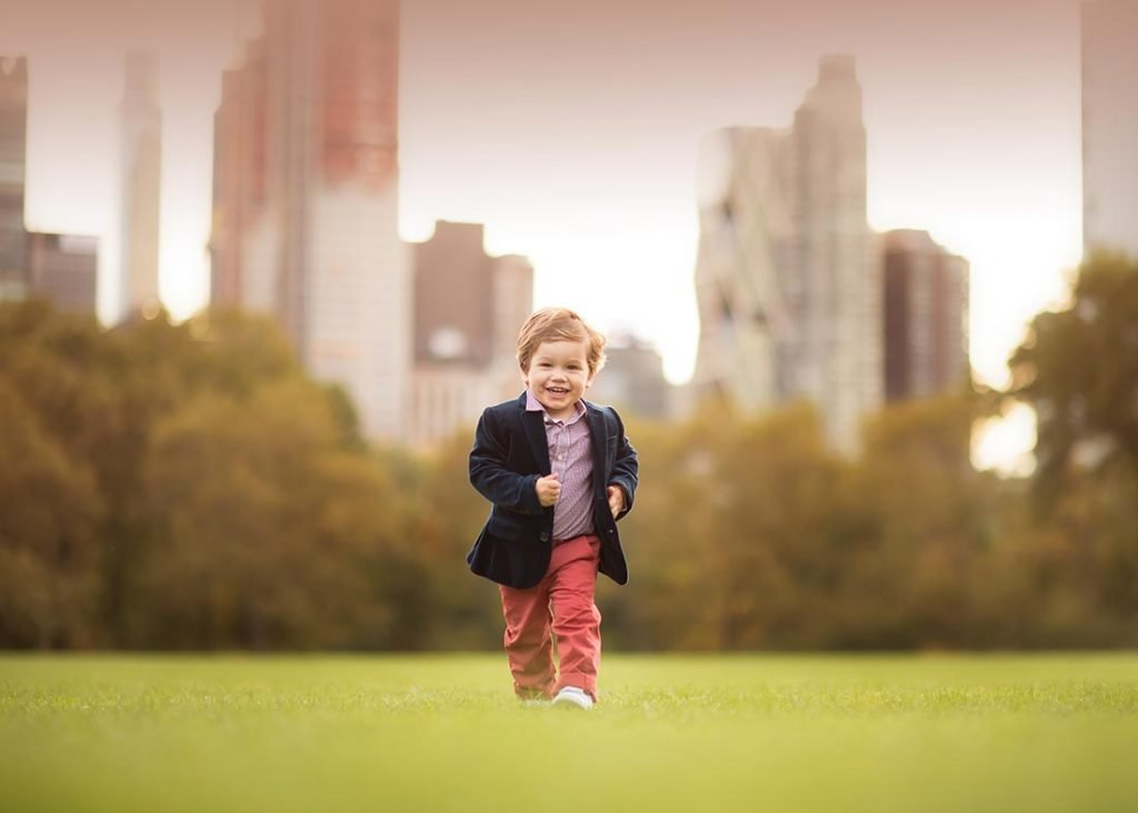 Stylish toddler running through a grass field in NYC's Central Park.
