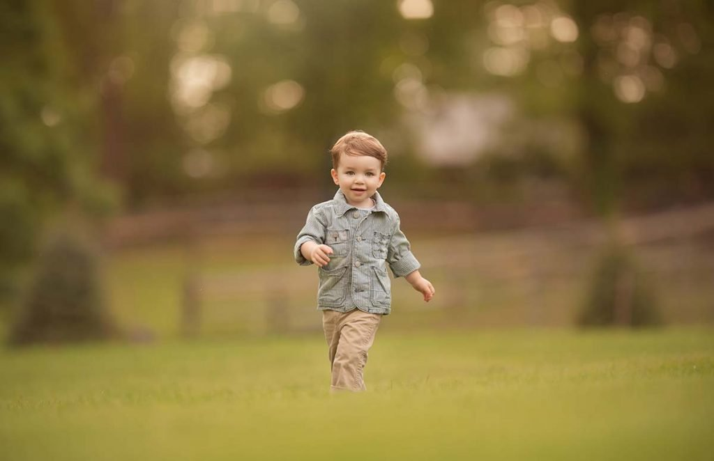 Happy boy running through a farm field.