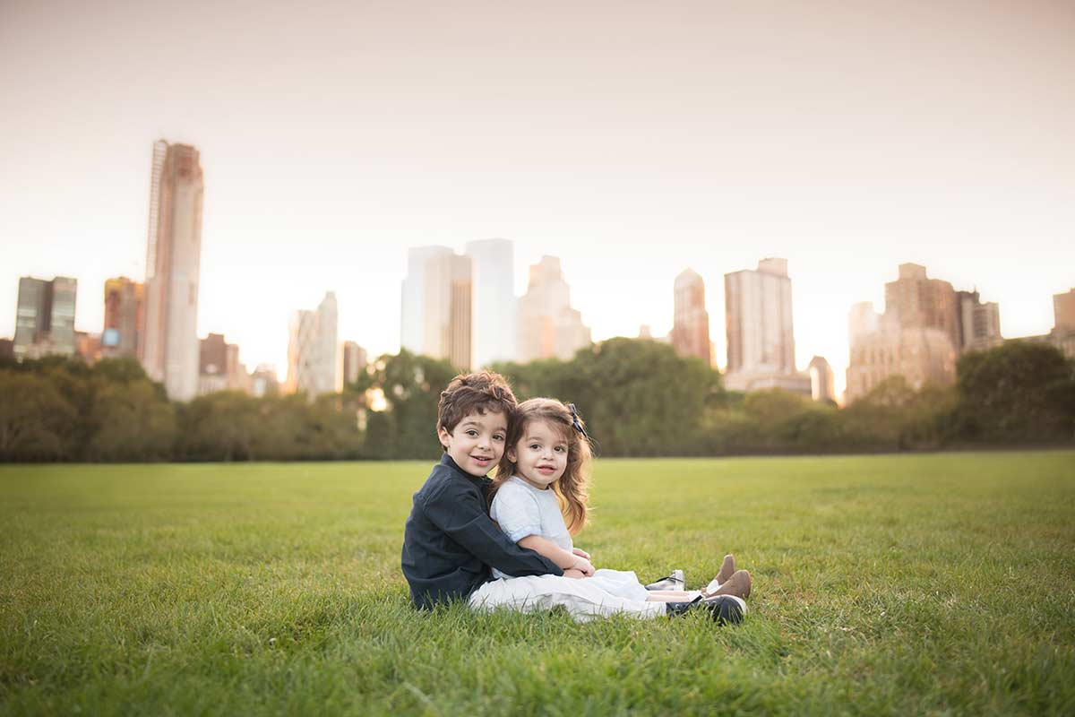 Two siblings holding hands while sitting in grass at NYC's Sheep Meadow.