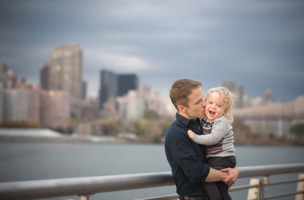 Dad kissing his little boy near the East River NYC.
