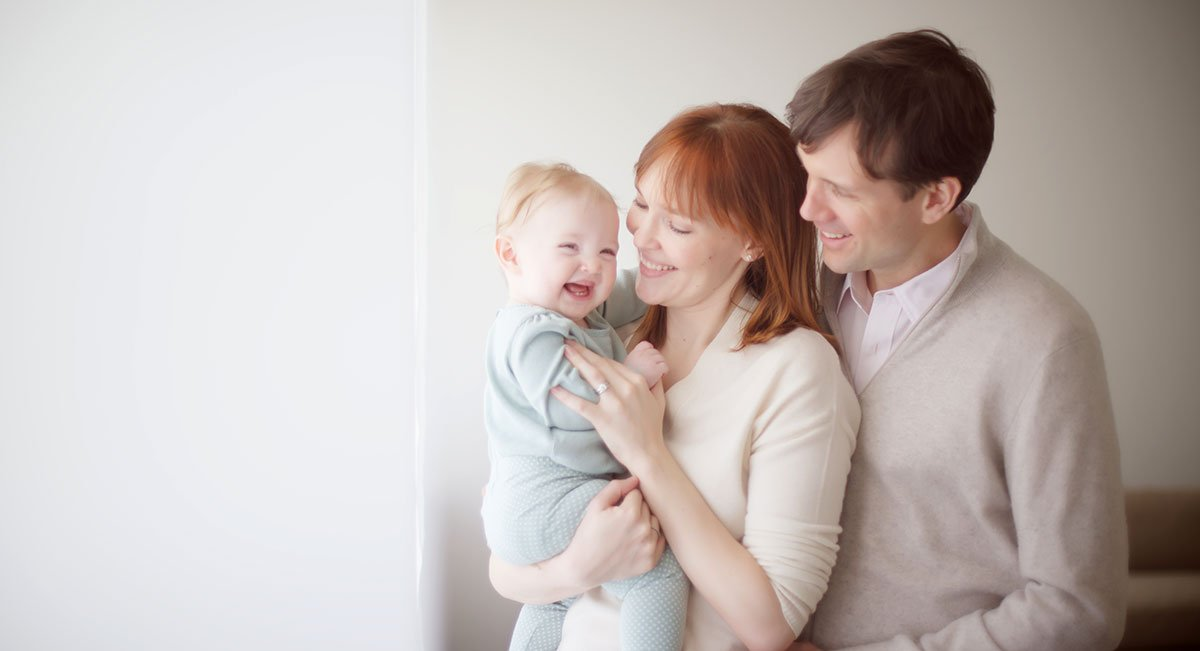 A modern family playing with their baby girl near a big window.