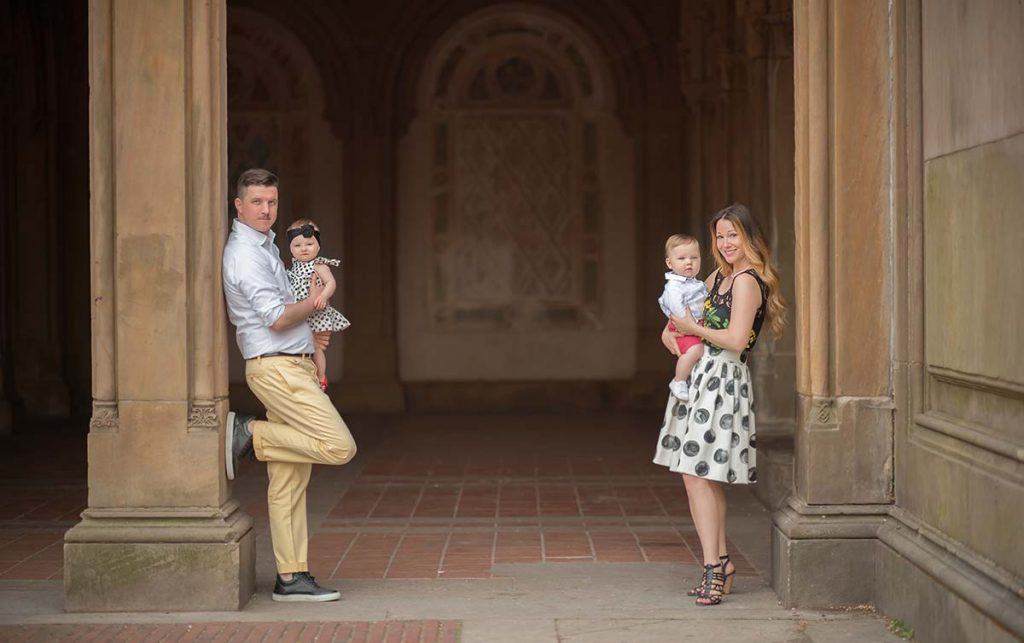 Portrait of a beautiful modern family with two children at Bethesda Fountain, NYC.