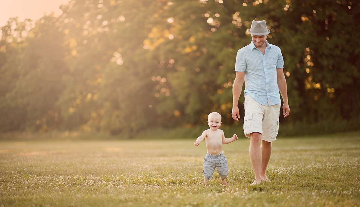 A father walking with his baby son in a field full of clovers.