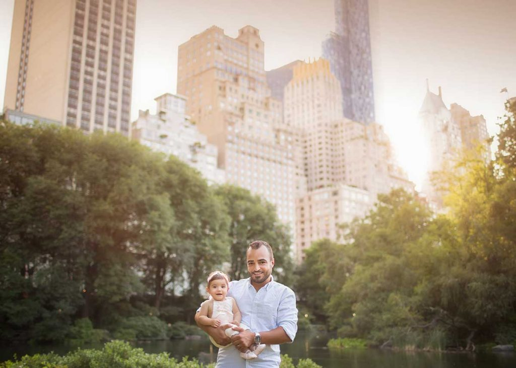A father holding his daughter pose in front of NYC skyline in Central Park.