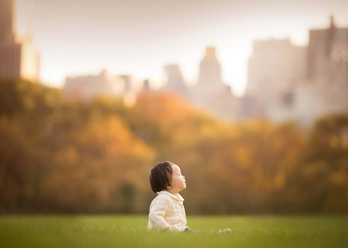 Lonely toddler sitting in grass in Central Park's Sheep Meadow.