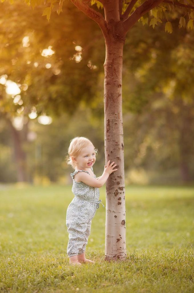 Little girl standing next to a tree in Central Park.
