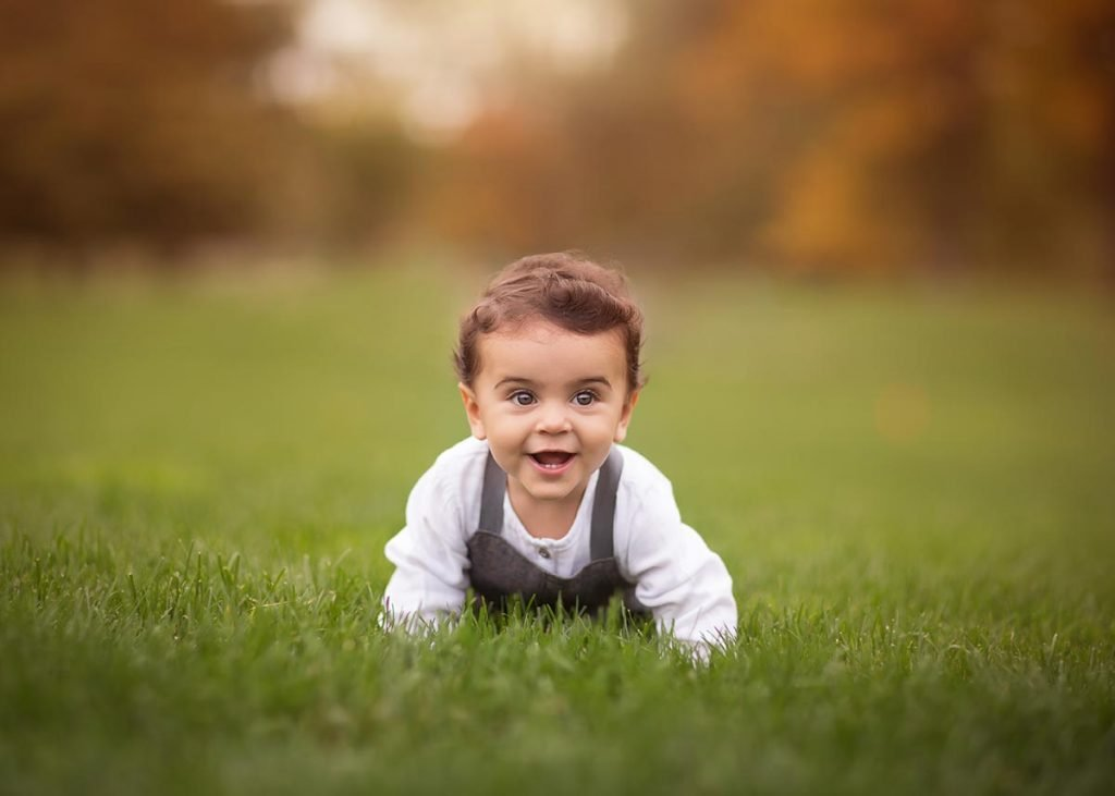 Happy toddler crawling through grass while smiling.
