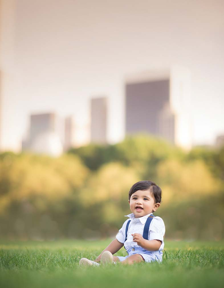 Young baby boy sitting in a lush grass field in NYC.