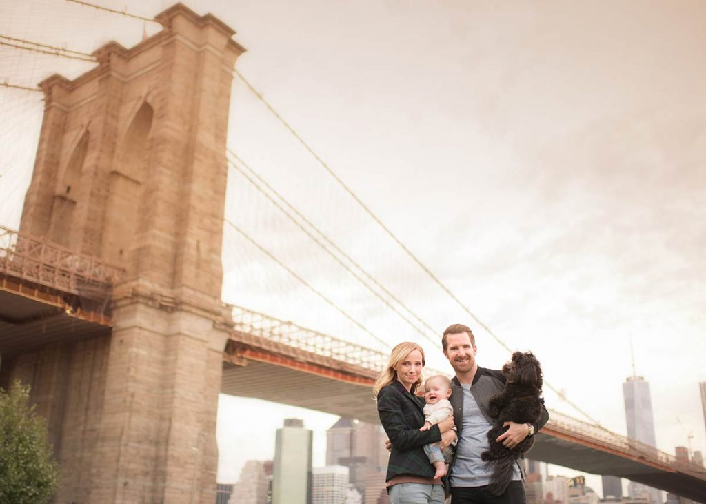 Modern family portrait in front of the Brooklyn Bridge, NYC.