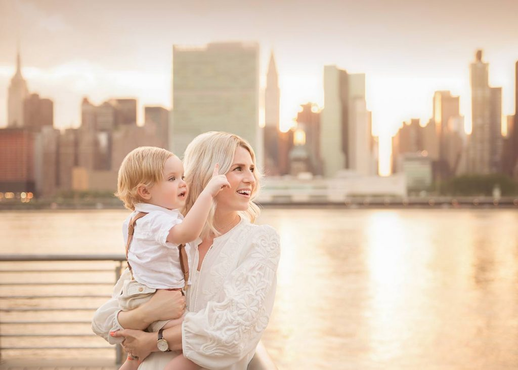 A mother holding her baby boy standing by the East River in NYC.