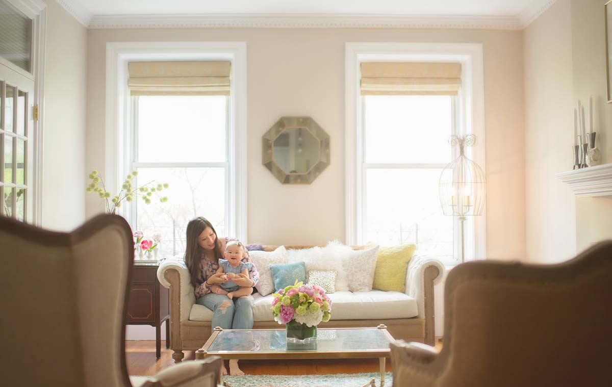 Lifestyle moment of mother and her little baby in a stylish living room setting.