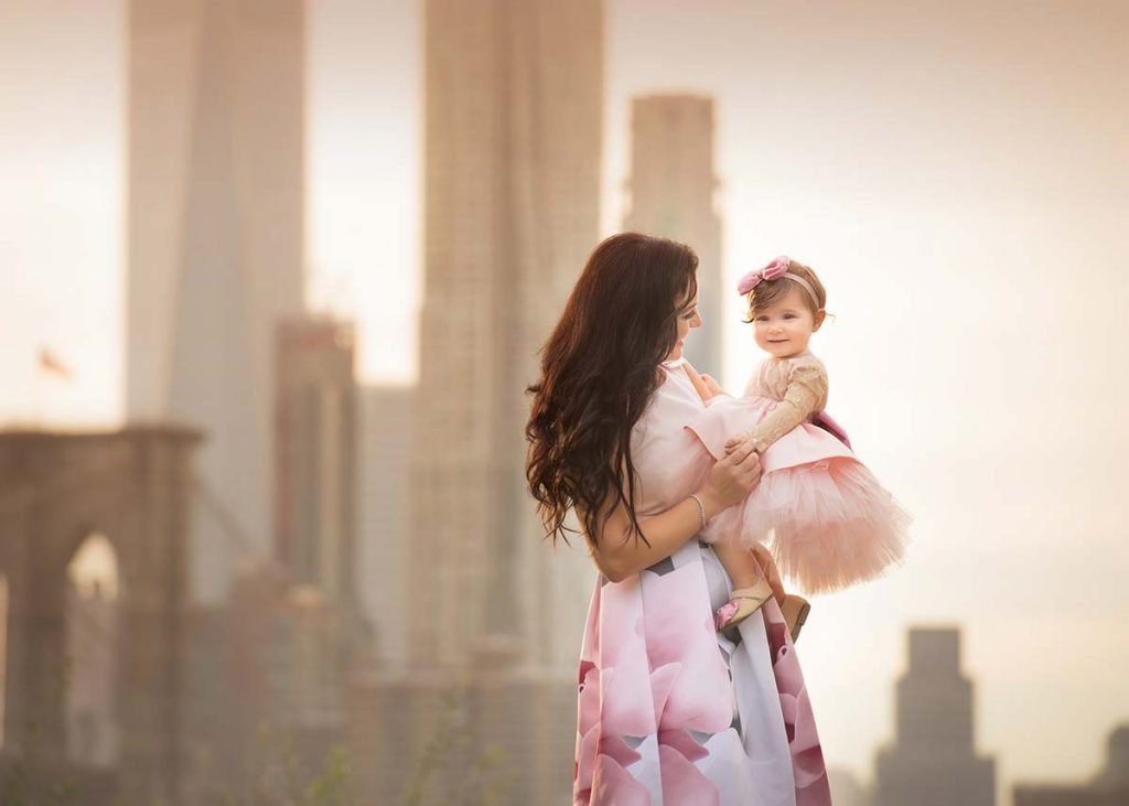 A mother and daughter posing by downtown NYC.