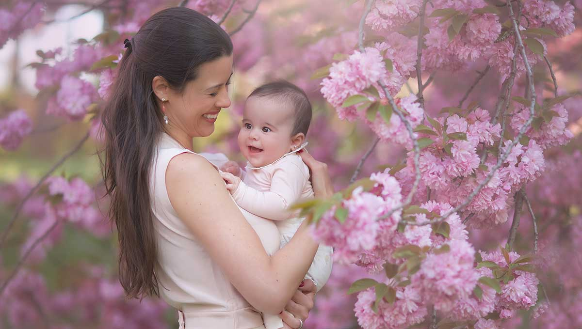 Mother holding her baby girl amongst cherry blossom trees.