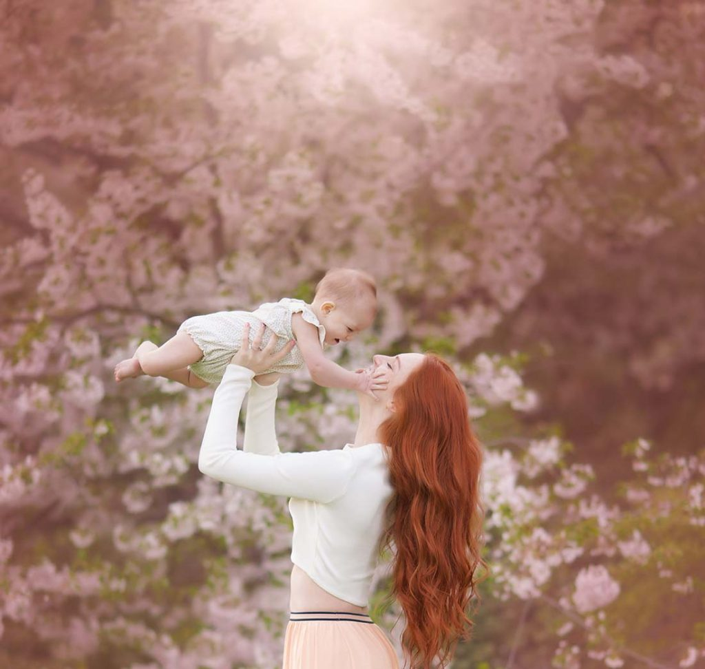 Mom in red hair holding up her baby amongst springtime cherry blossoms.