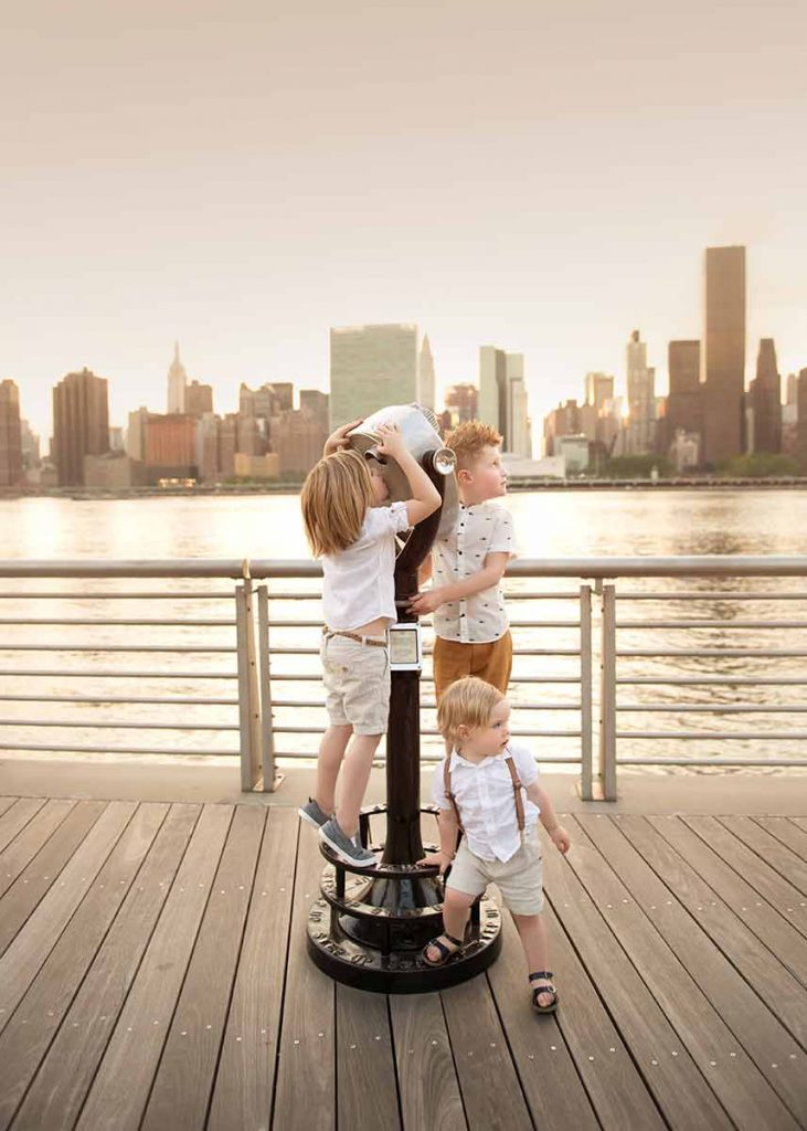 Lifestyle moment of three boys playing with a scope on a NYC waterfront.