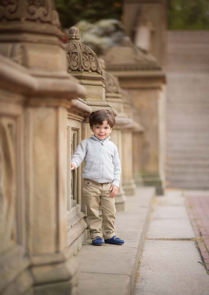 Handsome toddler standing near Bethesda Fountain in NYC's Central Park.