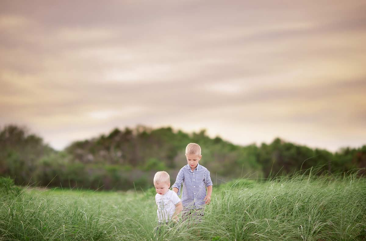Two young brothers walking through tall grass near a beach.