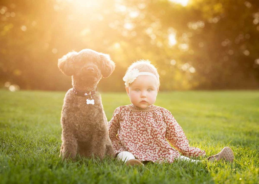 A toddler girl with headband posing for a baby portrait with her puppy in a park.
