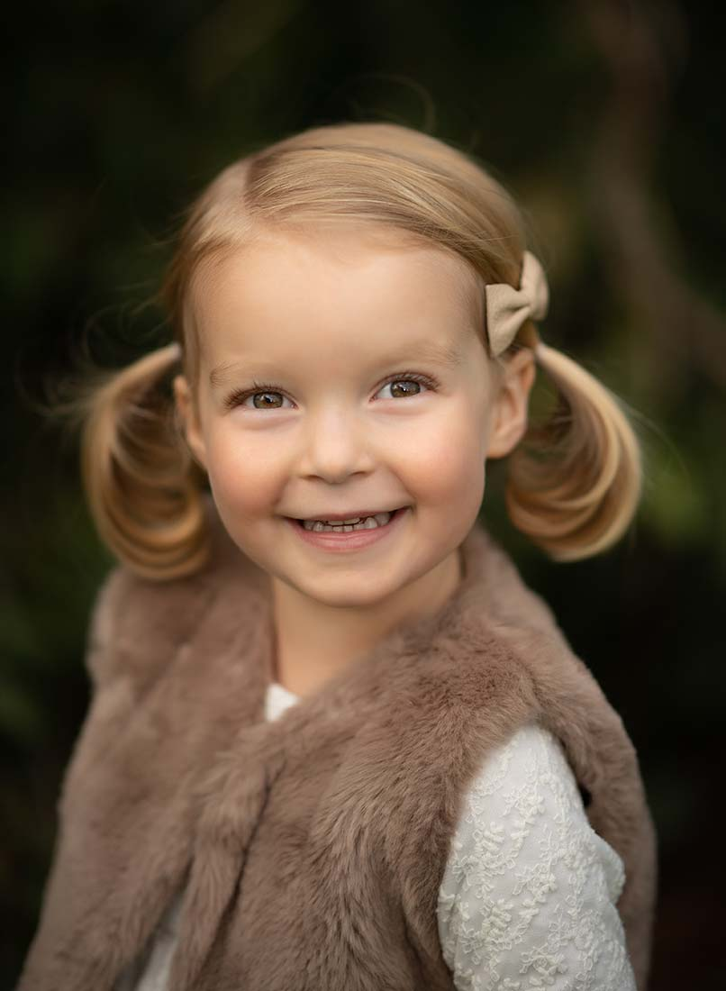 Young girl in ponytails smiling happily.