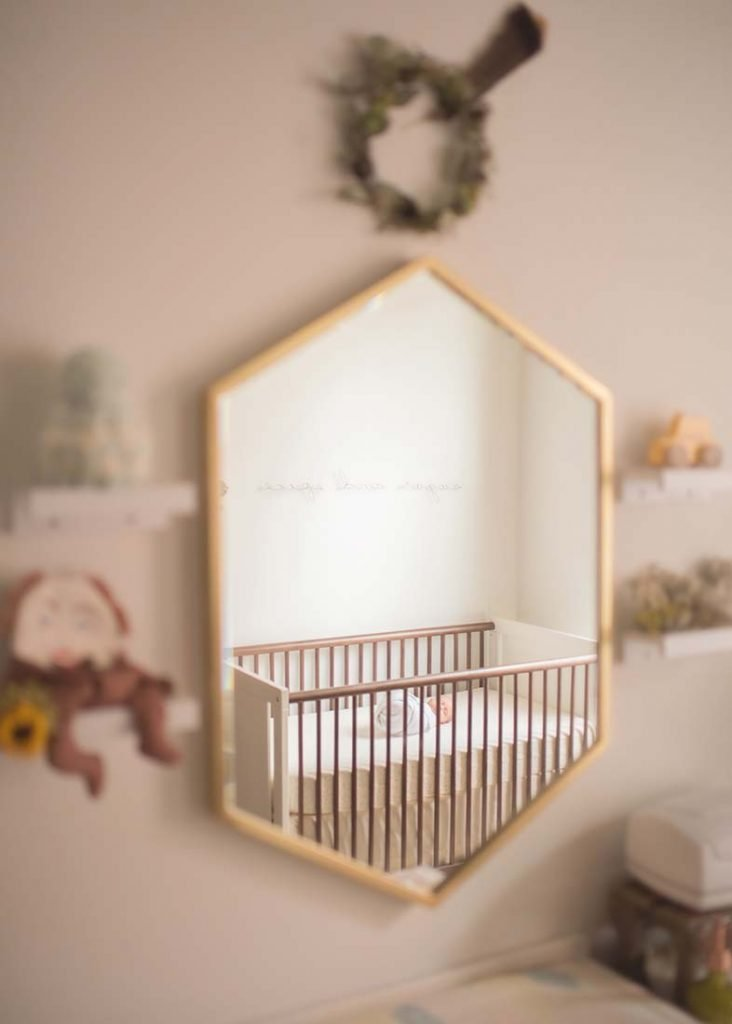 Reflection through a mirror of a baby sleeping in the crib